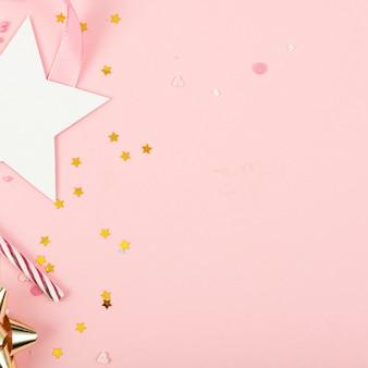 Surface de vacances de fête avec ruban, étoiles, bougies d'anniversaire et confettis sur surface rose