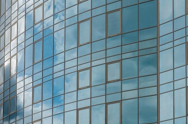 Surface de verre miroir gratte-ciel reflétant le ciel nuageux, surface sinueuse, fond d'architecture