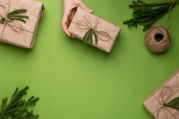 Surface verte avec des cadeaux écologiques avec des plantes vertes en papier kraft