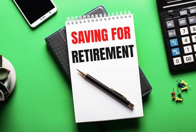 Sur une surface verte - un téléphone, une calculatrice et un journal avec l'inscription économisez pour la retraite