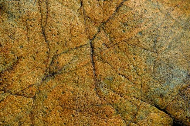 La surface d'un vieux rocher avec des fissures. texture de la vieille roche. fond sauvage
