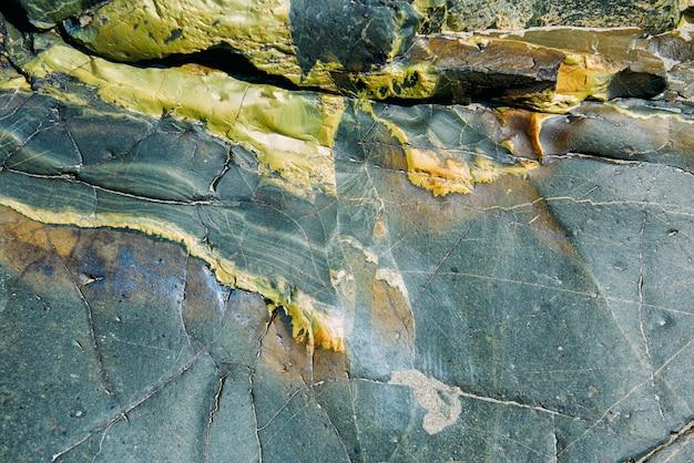 Surface d'un vieux rocher avec des fissures. texture de la vieille roche