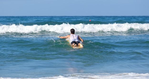 Surfer sur le longboard chevauche une vague dans la mer