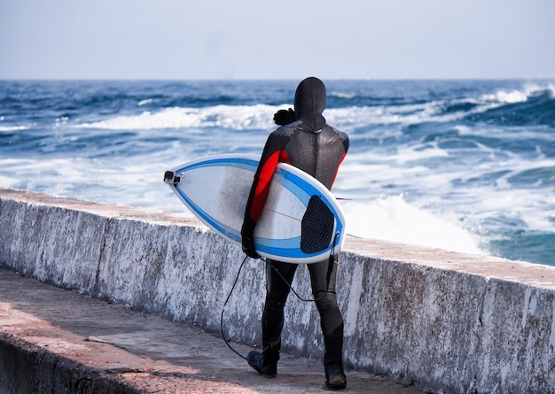 Surfer marchant dans l'eau portant une combinaison en hiver sur la jetée cold surf