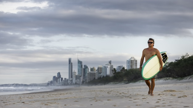 Surfer marchant avec planche de surf sur la plage paradisiaque des surfeurs
