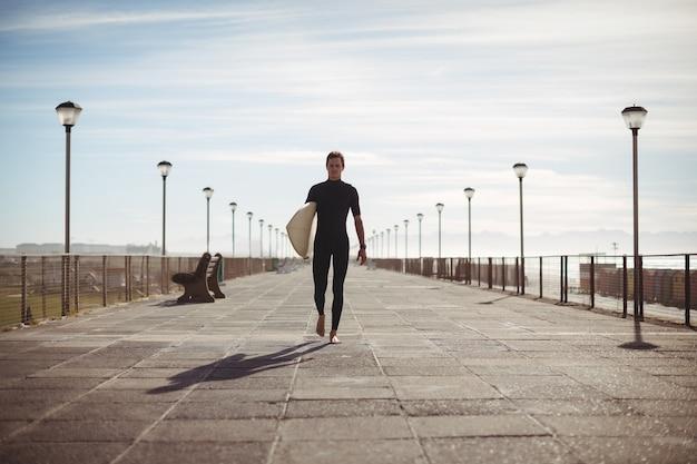 Surfer marchant avec planche de surf