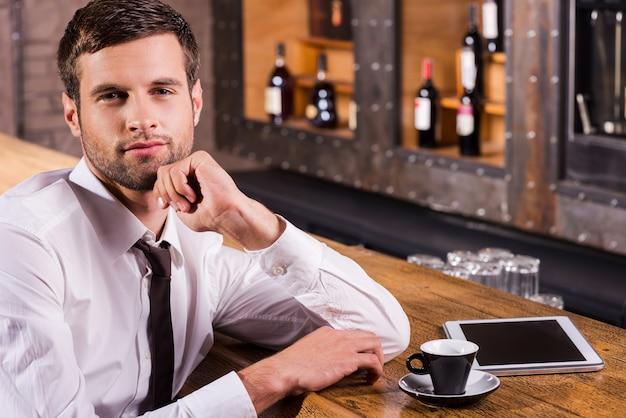 Surfer sur le net au bar. beau jeune homme en chemise et cravate tenant la main sur le menton et souriant alors qu'il était assis au comptoir du bar avec une tablette numérique posée près de lui