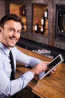 Surfer sur le net au bar. beau jeune homme en chemise et cravate travaillant sur tablette numérique et souriant assis au comptoir du bar