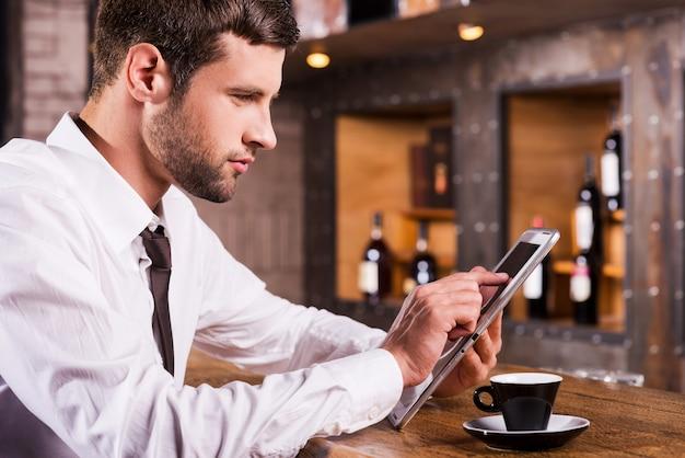 Surfer sur le net au bar. vue latérale du beau jeune homme en chemise et cravate assis au comptoir du bar et travaillant sur tablette numérique