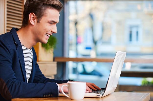 Surfer sur le net au café. vue latérale d'un beau jeune homme travaillant sur un ordinateur portable et souriant tout en dégustant un café au café