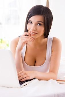 Surfer sur le net au lit. belle jeune femme souriante utilisant un ordinateur portable en position couchée dans son lit