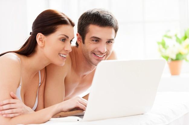 Surfer sur le net au lit. joyeux jeune couple d'amoureux allongé dans son lit et utilisant l'ordinateur ensemble