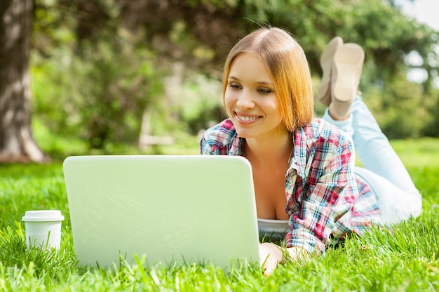 Surfer sur le net à l'extérieur. belle jeune étudiante travaillant sur ordinateur portable et souriant en position couchée sur l'herbe dans le parc