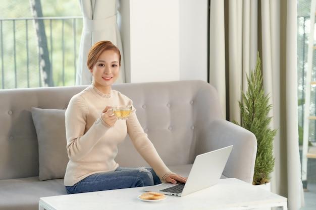 Surfer sur le net. jeune femme réfléchie en lunettes à l'aide d'un ordinateur assis sur le canapé à la maison