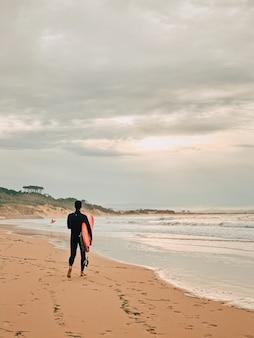 Surfer sur la plage de sable