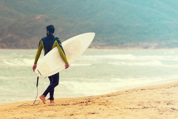 Surfer à seacoast, surfer avec sa planche de surf