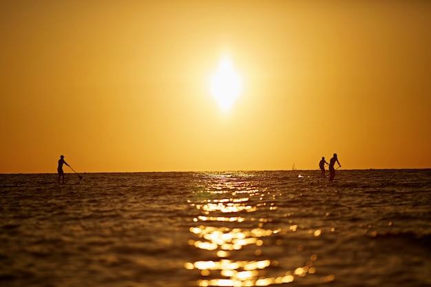 Surfer sous un magnifique ciel coucher de soleil sombre avec trois personnes.