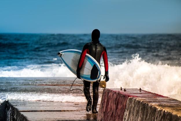 Surfer va dans l'eau portant une combinaison en hiver. surf à froid. éclaboussure de vague. combinaison imperméable