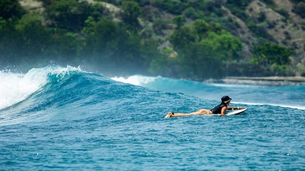 Surfer sur une vague bleue.