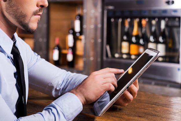 Surfer sur le web au bar. gros plan d'un homme en chemise et cravate travaillant sur une tablette numérique alors qu'il était assis au comptoir du bar