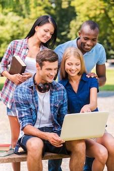 Surfer sur le web ensemble. quatre jeunes heureux discutant de quelque chose et regardant l'ordinateur portable tout en étant assis dehors ensemble