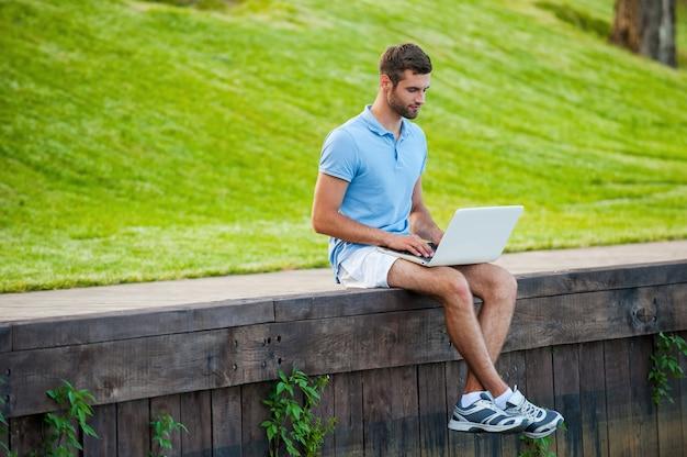 Surfer sur le web où il veut. beau jeune homme en polo travaillant sur ordinateur portable assis sur le quai