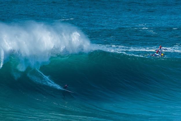 Surfers à cheval sur les vagues de l'océan atlantique vers le rivage à nazare, portugal
