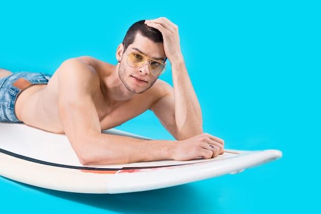 Surfeur attrayant, allongé sur la planche
