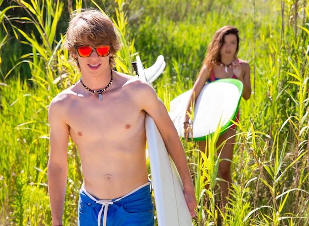 Surfeur garçon et fille marchant dans la jungle verte