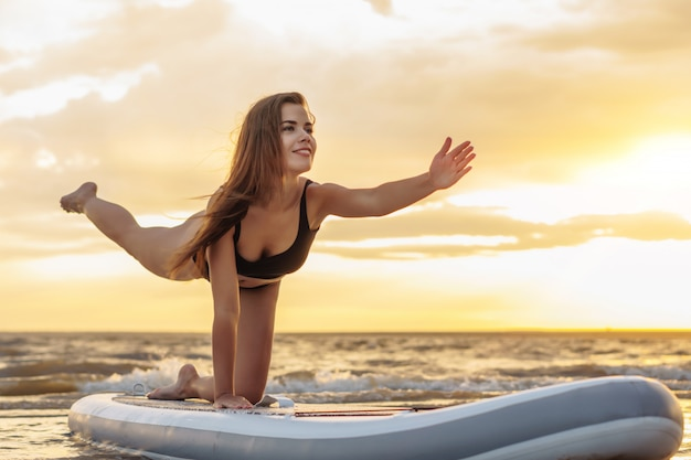 Surfeur de jeune femme sexy faisant du yoga sur sa planche de sup sur le coucher du soleil.