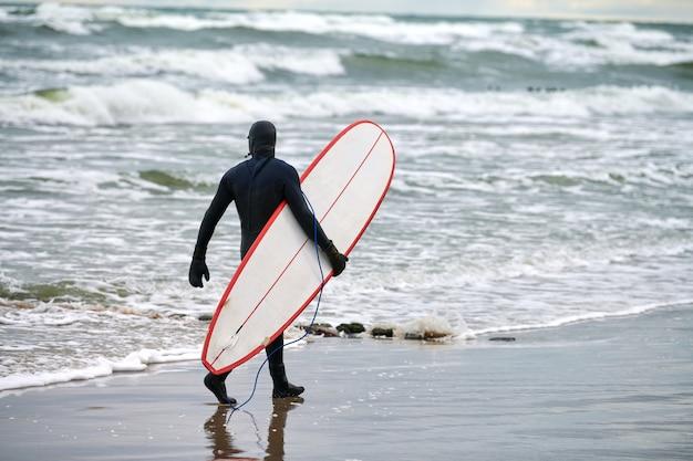 Surfeur masculin en maillot de bain noir marchant le long de la mer et tenant une planche de surf blanche à la main