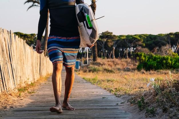 Un surfeur méconnaissable descend la passerelle en bois jusqu'à la plage avec une planche de surf au lever du soleil