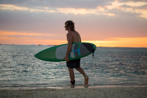 Surfeur de paddle board silhouette sur fond de coucher de soleil