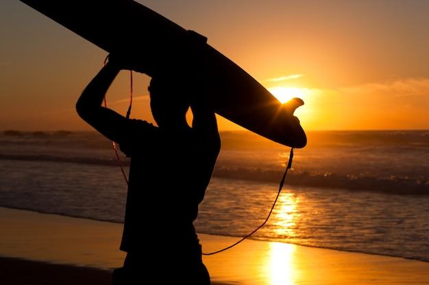 Surfeur et planche au soleil couchant