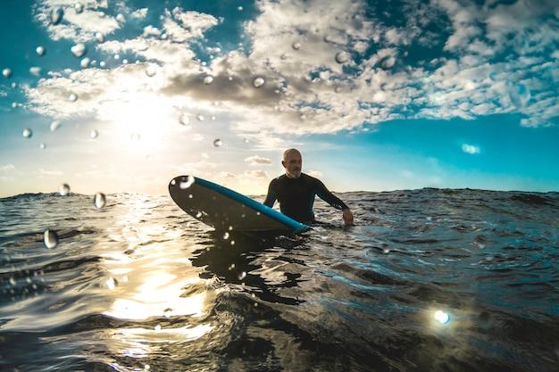 Surfeur se détendre sur une planche de surf au coucher du soleil à tenerife en attendant la prochaine bonne vague