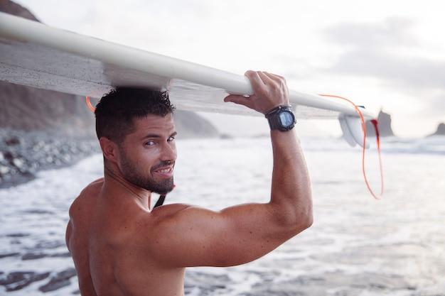 Un surfeur séduisant sourit avec sa planche de surf posée sur la tête, il est à la plage. homme caucasien sportif et musclé.