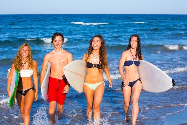 Surfeurs adolescents garçons et filles qui sortent de la plage