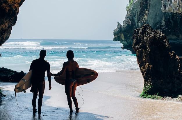 Surfeurs entrant dans la mer, prêts à surfer sur les vagues. plage de kuta, bali.
