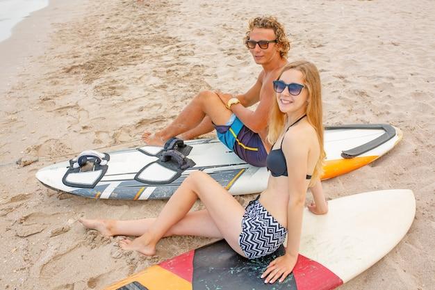 Surfeurs à la plage - couple souriant de surfeurs marchant sur la plage et s'amusant en été