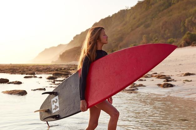 Une surfeuse inspirée porte une planche de surf