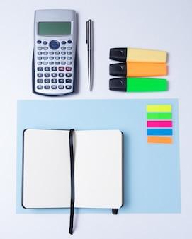 Surligneurs colorés, stylo, marqueurs, calculatrice et papier vierge pour travailler ou étudier