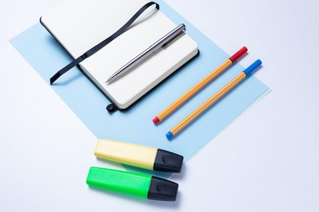Surligneurs colorés, stylos, marqueurs, bloc-notes et papier vierge pour travailler ou étudier