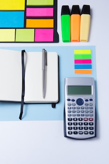 Surligneurs colorés, stylos, marqueurs, calculatrice, cahier et papier vierge pour travailler ou étudier