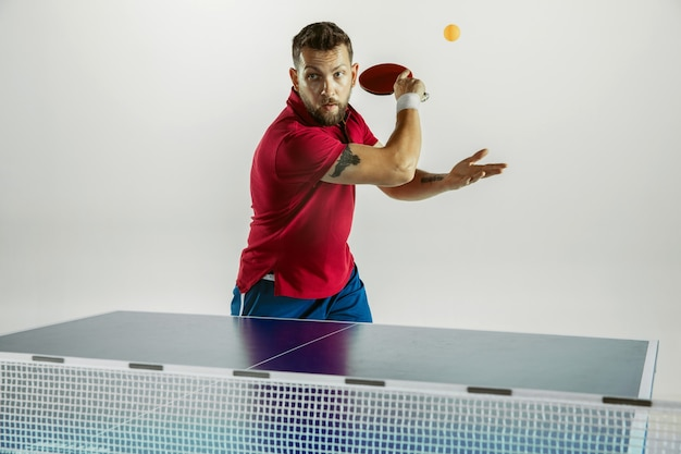 Surmonter. jeune homme joue au tennis de table sur mur blanc. le modèle joue au ping-pong. concept d'activité de loisirs, sport, émotions humaines dans le jeu, mode de vie sain, mouvement, action, mouvement.