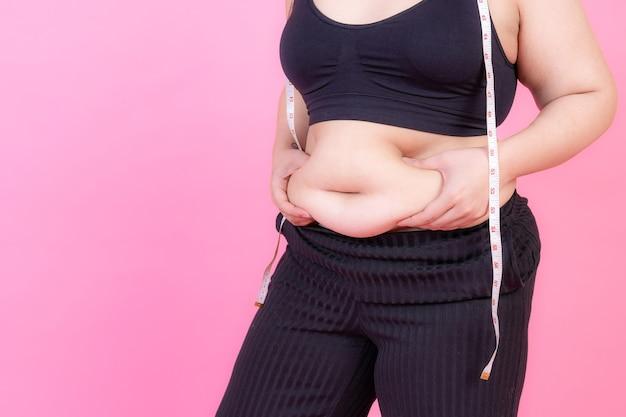 En surpoids presser la graisse du ventre avec un ruban à mesurer sur son cou