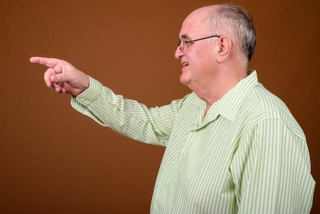 Surpoids senior man wearing eyeglasses contre mur marron
