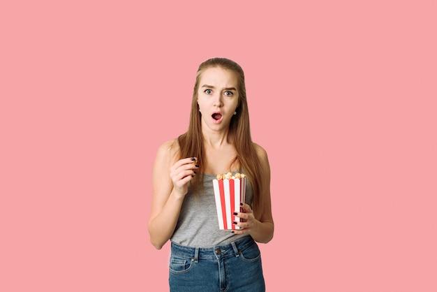 Surprenant femme mangeant du pop-corn. fille tenant une grande boîte rayée avec une partie cinéma de pop corn sur mur rose. sensationnel