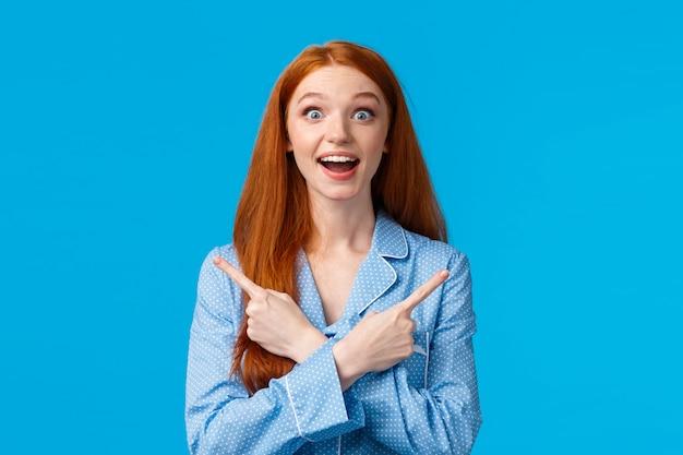 Surpris et amusé belle adolescente rousse, étudiante jouant avec des colocataires en vêtements de nuit, pointant à gauche et à droite, sur le côté avec les mains croisées étonné, voir beaucoup de choix