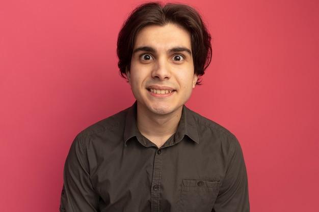 Surpris à l'avant jeune beau mec portant un t-shirt noir isolé sur un mur rose