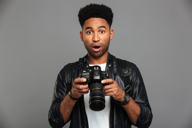 Surpris beau afro-américain en veste de cuir tenant un appareil photo numérique